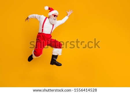 Full body profile side photo of crazy funky grey hair bearded grandfather hipster in red hat jump run enjoy x-mas time party  wear black boots isolated yellow color background #1556414528