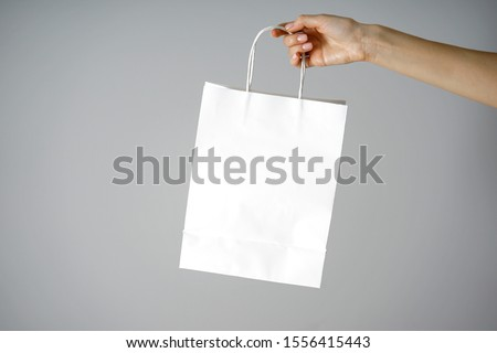 Paper white craft bag, eco packaging in a female hand, on a gray background, with place for text. #1556415443