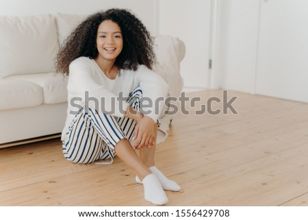 Indoor shot of restful happy African American woman sits on floor in living room, white sofa in background, wears fashionable clothes and socks, expresses positive emotions, rests at home alone #1556429708