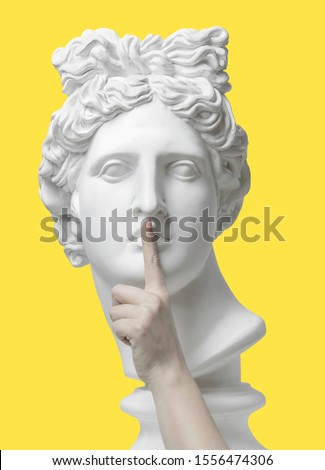 Sign of silence. Gypsum statue of Apollo's head, holding finger on his lips. Statue. Keep silence. The secret concept. Pandemic. Social distancing. Black Lives Matter. Coronavirus Covid-19 outbreakin #1556474306