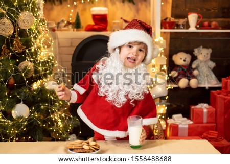 Happy new year. Santa in home. Little Santa Claus kid with beard and mustache. Cheerful Santa Claus holding glass with milk and cookie with fireplace and Christmas Tree in the background #1556488688