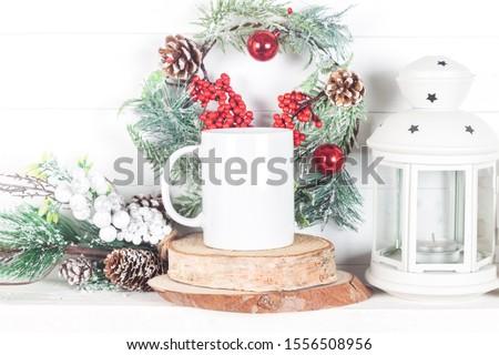 Christmas mockup of a white mug for display of design - mug on a mantelpiece with a Christmas wreath and a lantern