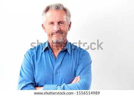 Studio Shot Of Mature Man Against White Background Smiling At Camera #1556514989