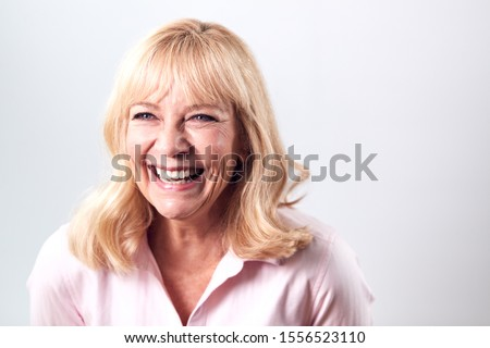 Studio Shot Of Smiling Mature Woman Against White Background At Camera #1556523110
