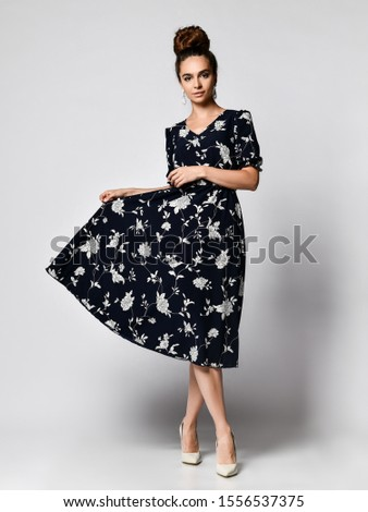 Slim curly female model in a silk pale dark dress looking at the camera in full growth. . Cute girl in romantic clothes is going on a date, smiling pretty on a white background. #1556537375