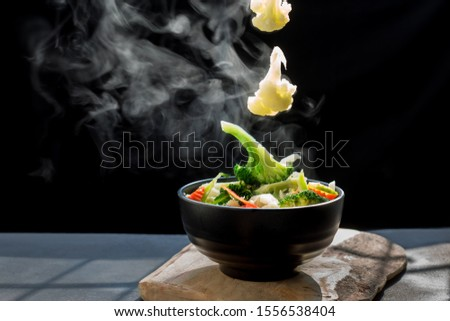The steam from the vegetables carrot broccoli cauliflower on black bowl , a steaming. Boiled hot Healthy food on table on black background,hot food and healthy meal concept #1556538404