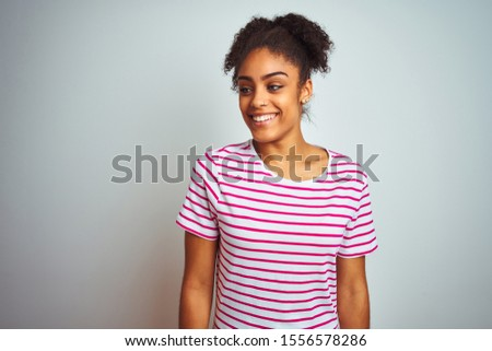 African american woman wearing casual pink striped t-shirt over isolated white background looking away to side with smile on face, natural expression. Laughing confident. #1556578286