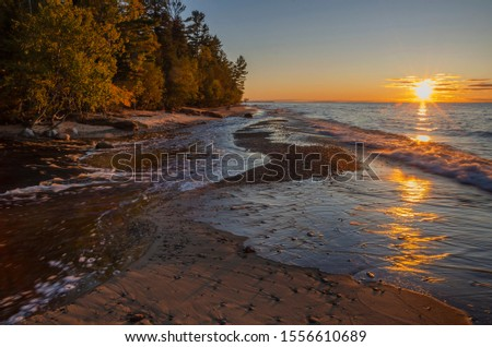The Hurricane River pours out of the forest and empties into Lake Superior at sunset, Pictured Rocks National Lakeshore, Alger County, Michigan
