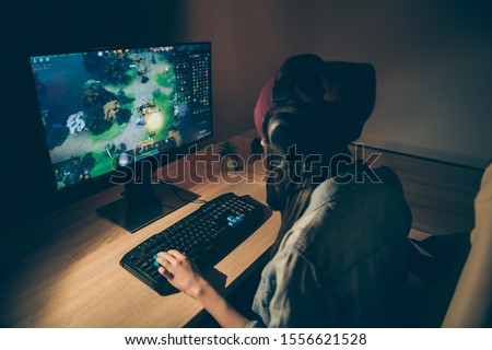 Back rear view photo of girlfriend playing video game with their friends speaking with them in front of keyboard