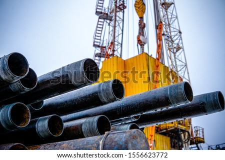 Oil Drill pipe. Rusty drill pipes were drilled in the well section. Downhole drilling rig. Laying the pipe on the deck. View of the shell of drill pipes laid in courtyard of the oil and gas warehouse. #1556623772