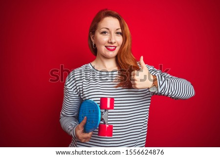Young redhead student woman holding skate over red isolated background happy with big smile doing ok sign, thumb up with fingers, excellent sign