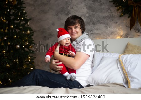 father and baby on bed at home on Christmas holidays #1556626400