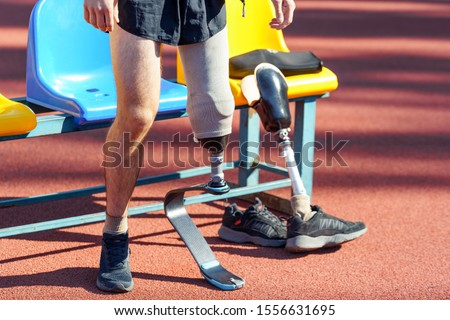 Sportsman with prosthetic leg standing near seats and getting ready for a running race. Disabled people with active lifestyle. #1556631695