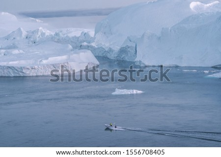 Icebergs and tourist fishing boat in Greenland iceberg landscape of Ilulissat icefjord with giant icebergs. Icebergs from melting glacier. Aerial drone photo of arctic nature. #1556708405