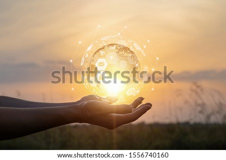Concept support global business. Hand showing business icons and globe at sunset. #1556740160
