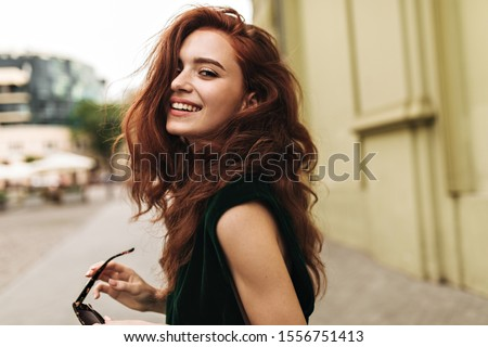 Attractive woman in dark green outfit smiling outside #1556751413