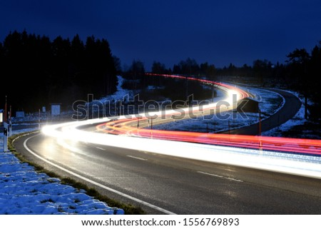 Long Exposure of driving cars on a curvy road in the black forest at snow (1)