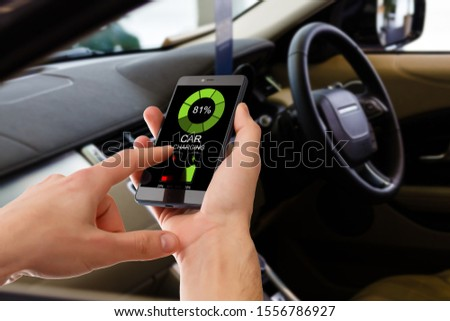 Charging Electric car Looking at App On Mobile Phone. Close up of smartphone screen. Hand holding smart device. Mobile application for eco transportation #1556786927