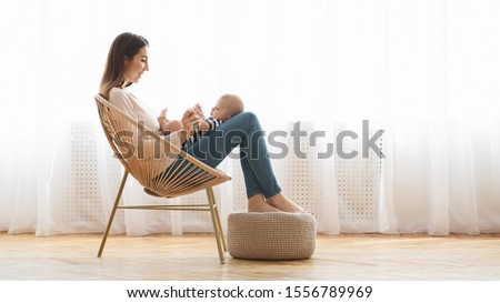 Young woman relaxing in wicker chair with her infant baby on laps, panorama with free space #1556789969
