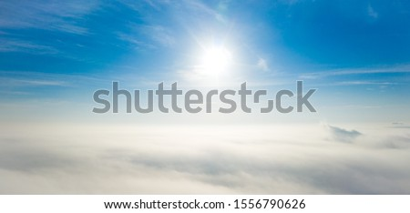 Aerial photo above the fog or white clouds with shining sun. Beautiful sunrise cloudy sky from aerial view. Above clouds from airplane window or drone. #1556790626