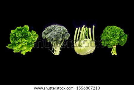 Assorted green vegetables on black background. Salad, broccoli, parsley and cherub neatly aligned on a dark surface. #1556807210