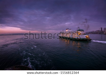A Seattle to Bainbridge Island Ferry Boat in the early morning hours Royalty-Free Stock Photo #1556812364