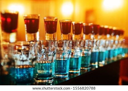Blue bomb drinks shot glasses standing on the counter falling with big splash #1556820788