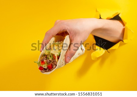 Hand holding a taco through a torn hole in yellow paper background. Hot price, discount on favorite Mexican dishes.