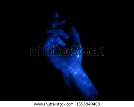 A hand glows with blue magic, revealing veins beneath the skin. #1556840408