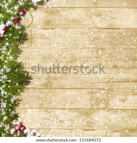 Christmas fir tree with snowfall  on a wooden board