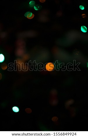 Defocused colored Christmas lights on Christmas tree dark background #1556849924