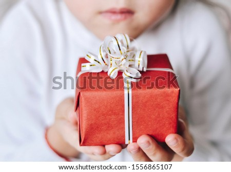 Close up of female hand holding a red gift box wrapped and decorated with white bow, ribbon. Small gift in the hands of little girl present for Christmas, Valentine Day, New Year, birthday. Top view #1556865107