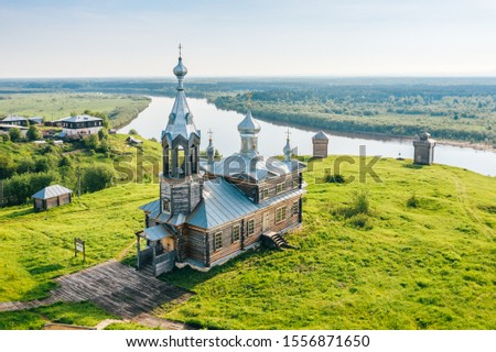 Old russian orthodox church made of wood on hill top near river in Cherdyn village, aerial view. Rural landscape with historic christian religious building in Perm krai, Ural, Russia Royalty-Free Stock Photo #1556871650