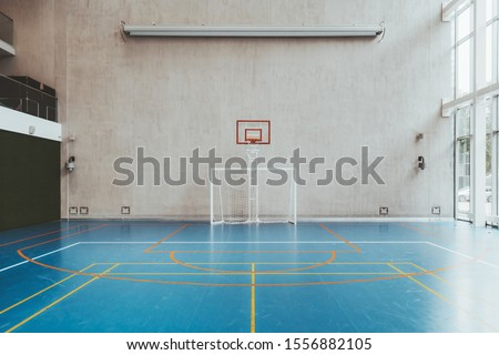 Front view of the court in the gymnasium hall; an indoor modern office stadium with a basketball basket and hoop, football goal, blue floor, a concrete wall with an undeployed projection screen above #1556882105