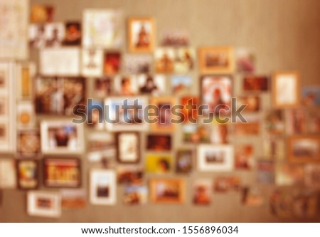 Collage of pictures with loved ones, friends or family. Blurred background with postcards and photos in frames put up on a wall. Concept for keeping good memories about holidays or vacation.
