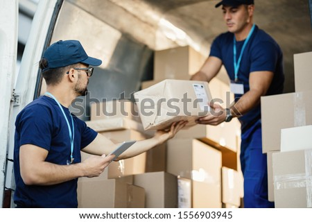 Young courier using touchpad while loading packages with his coworker in a delivery van.  Royalty-Free Stock Photo #1556903945