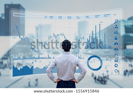 Finance trade manager analysing stock market indicators for best investment strategy, financial data and charts with business buildings in background #1556915846