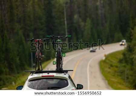 Selective focus on bicycles on roof top while driving on the highway. Safety road equipment for bike transport. Road and woods at background Royalty-Free Stock Photo #1556950652