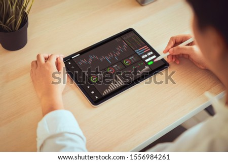 Stock exchange market concept, businessman trader looking on tablet with graphs analysis candle line in office room, diagrams on screen. #1556984261