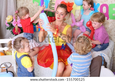 Five happy kids and facilitator make dogs of long balloons at children party. Inscription Happy Birthday on wall.