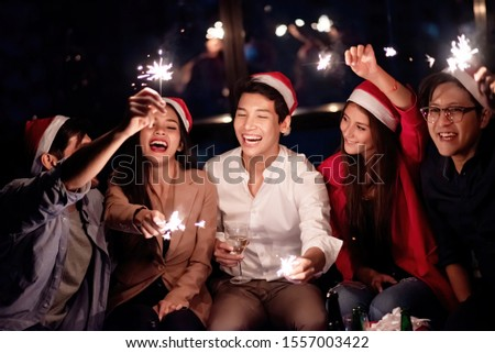 Ethnically diverse group of employees are celebrating Christmas party at the office. #1557003422