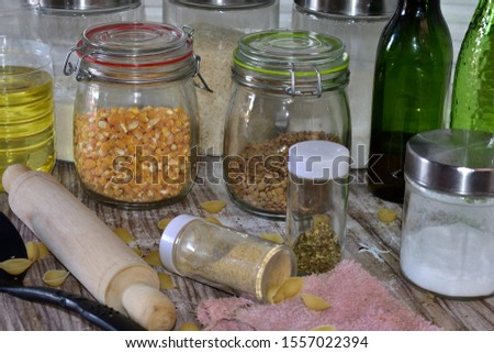 Set of glass cylindrical kitchen containers on a wooden table with cereals a spoon and a rolling pin   #1557022394