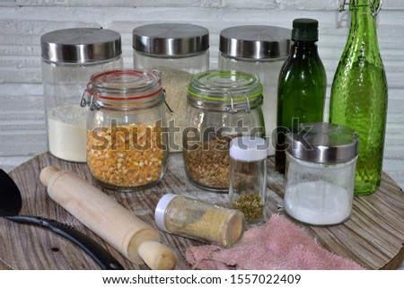 Set of glass cylindrical kitchen containers on a wooden table with cereals a spoon and a rolling pin   #1557022409