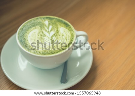 hot matcha green tea latte on wood table. delicious beverage #1557065948