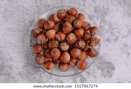 Nuts. Heap of hazelnuts on a plate. Top view. Close-up. Food photography. #1557067274