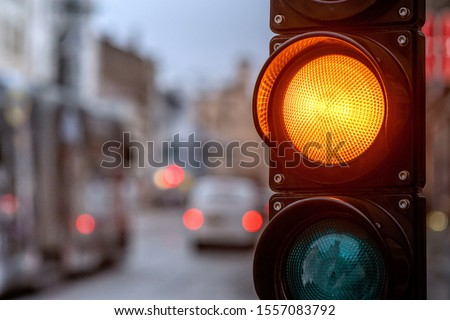 A city crossing with a semaphore. Orange light in semaphore - image #1557083792