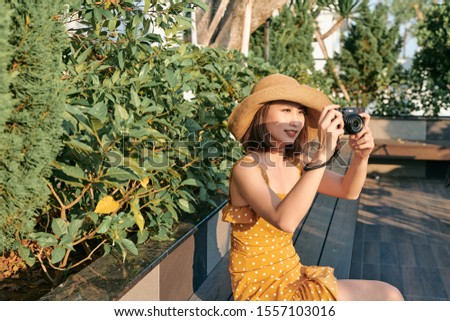 Fashionably dressed woman sitting in the park and using camera