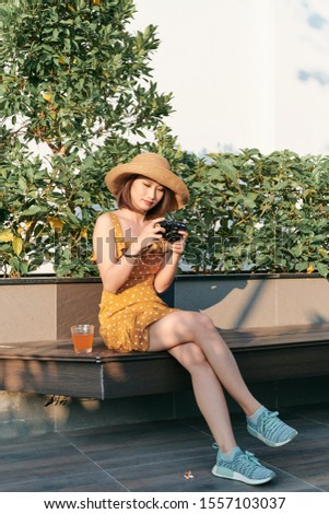 Fashionably dressed woman sitting outside and using camera
