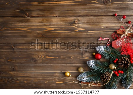 Fir branch with Christmas decorations on old wooden brown background with copy space for text