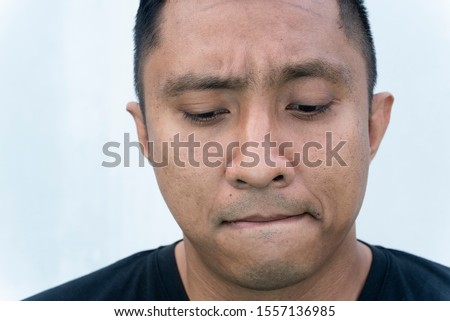 Face of an Indonesian man of Asian heritage on white background who looks ashamed, guilty. He bends his face downward.  So embarrassed his eyes look at the floor while biting his tongue   #1557136985